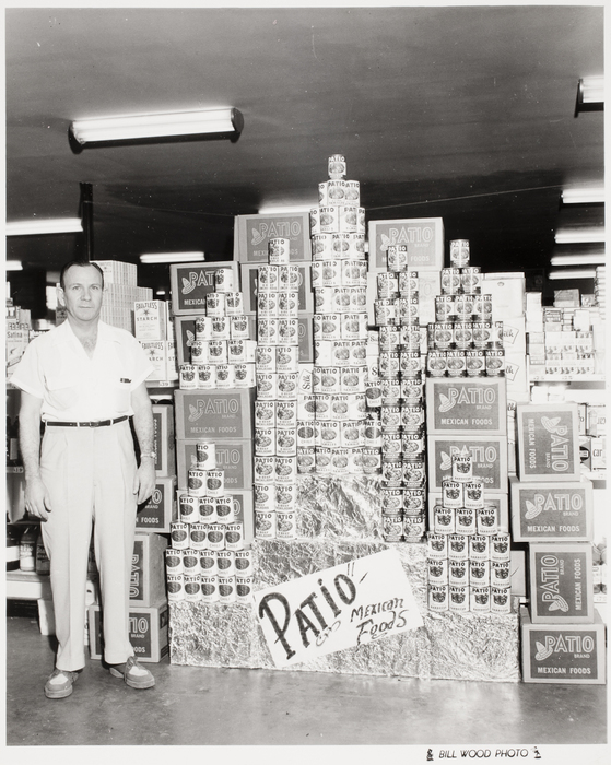 [Man with Display of Patio Mexican Foods Canned Products]