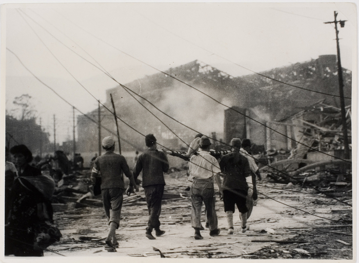 [Around 6:00 a.m., 1500 meters from epicenter of blast, men carry a body while searching for survivors amid ruins, following dropping of atomic bomb on Nagasaki]