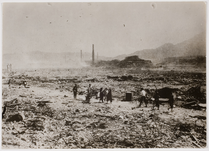 [Distant of survivors of atomic blast walking along road amid ruims of city, looking for relatives, following dropping of atomic bomb on Nagasaki, Japan.]