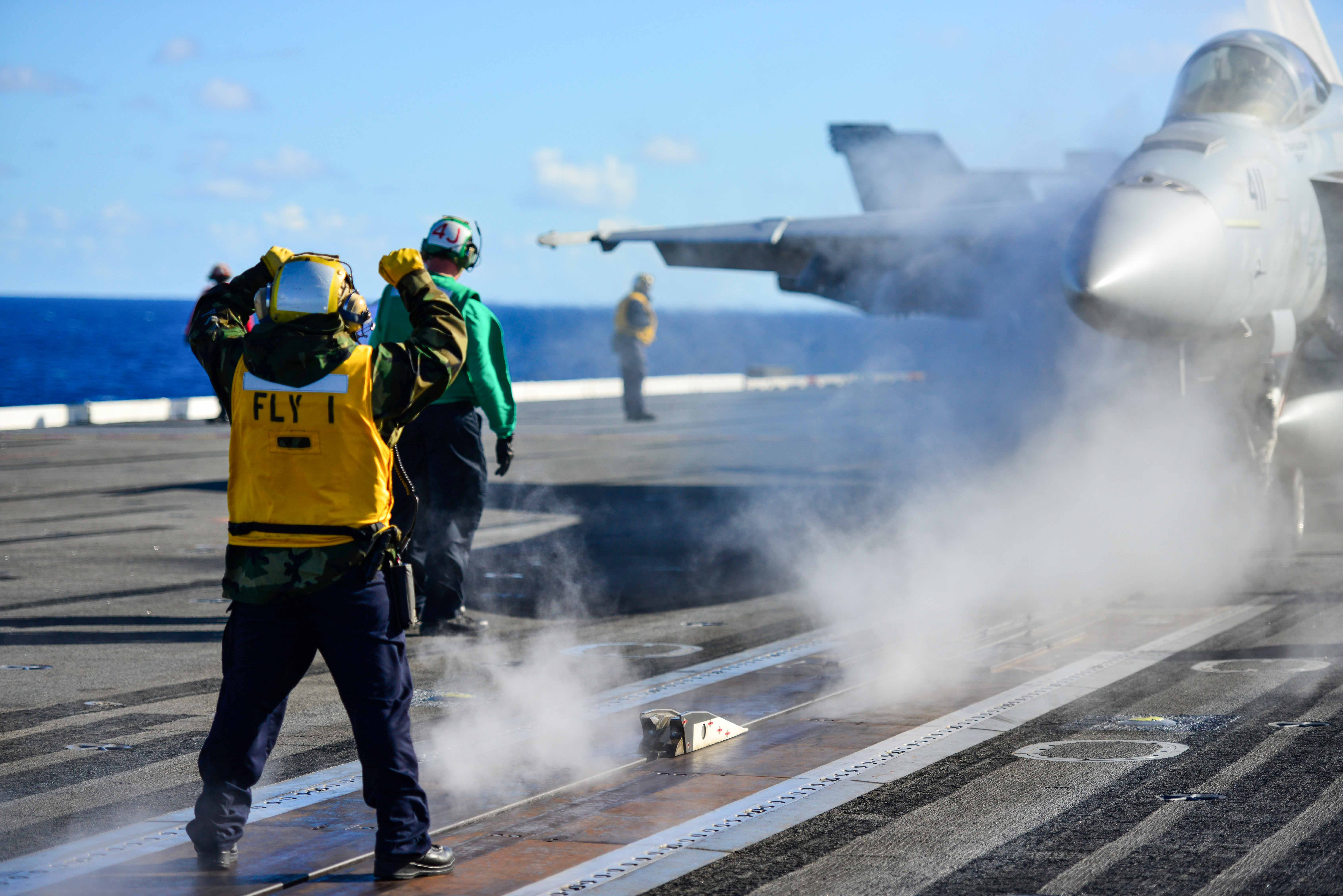 PACIFIC OCEAN (Dec. 13, 2014) Aviation Boatswain's Mate (Handling) 2nd Class Myron Aldan directs an aircraft onto a catapult on the flight deck of the Nimitz-class aircraft carrier USS John C. Stennis (CVN 74). John C. Stennis is undergoing an operational training period in preparation for future deployments. (U.S. Navy photo by Mass Communication Specialist 3rd Class Ignacio D. Perez/Released)