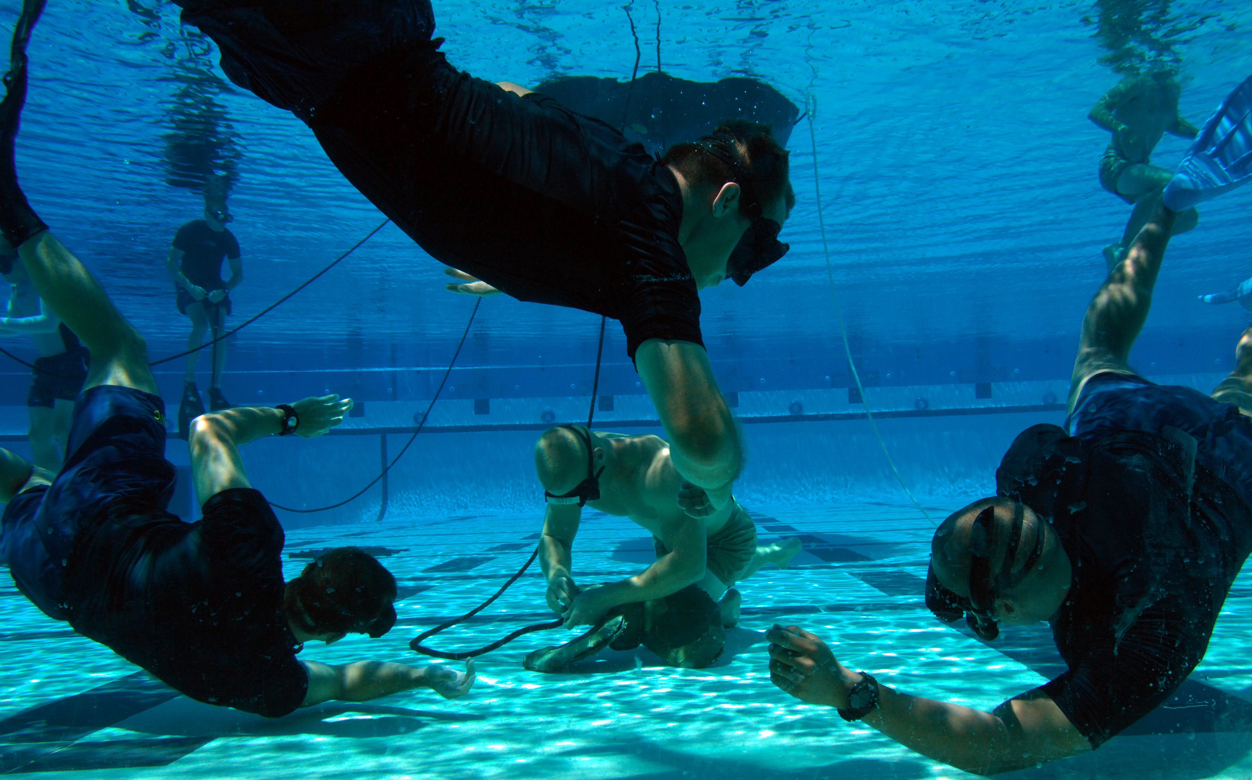 Instructors watch a Basic Crewman Training (BCT) student demonstrate knot-tying skills during water proficiency training at Naval Amphibious Base Coronado. BCT is the first phase of the Special Warfare Combatant-Craft Crewman (SWCC) training program. SWCCs operate and maintain the Navy's inventory of state-of-the-art, high-performance boats used to support SEALs in special operations missions worldwide. U.S. Navy photo by Mass Communication Specialist 2nd Class Christopher Menzie (Released)