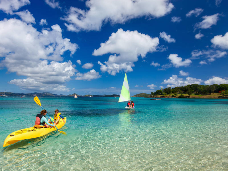 Family travel   mother and son paddling on colorful yellow kayak at tropical ocean water during summer vacation