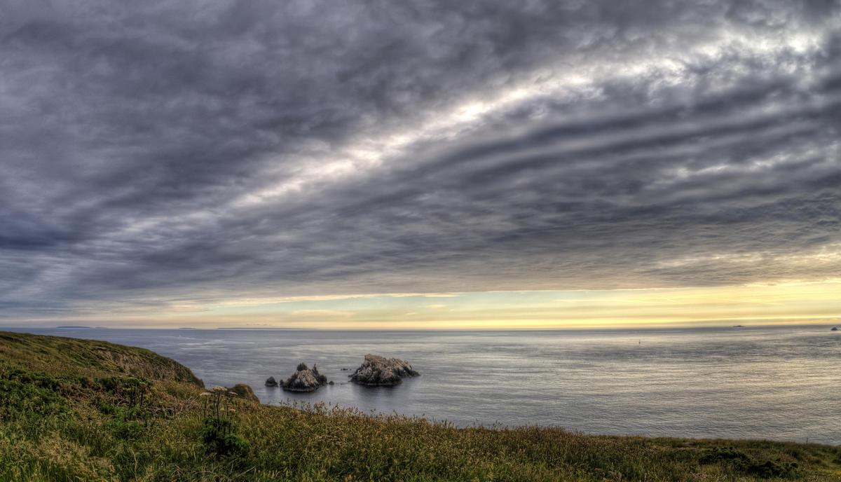 The Gannet Rocks on Alderney under the edge of overcast by Neil Howard via Flickr Creative Commons