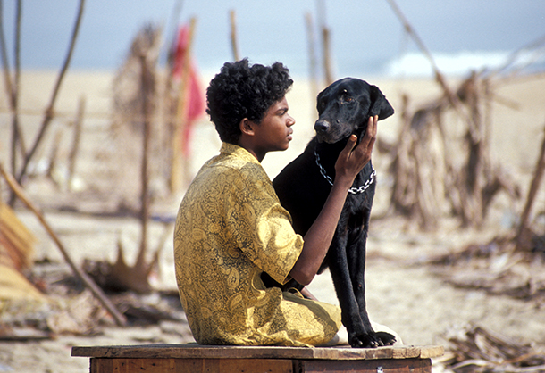 A boy named Emmanuel holding his dog amid the debris from a devastating tsunami