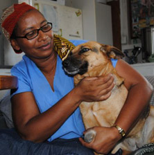 One of the project's resident dogs, wakes up from a slumber and ambles over to Maria for some cuddling and love.