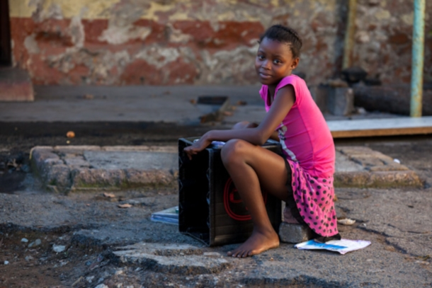 A school girl sits on stones and uses a plastic container as a desk to do her homework on at the hostel. c. Julia Cumes