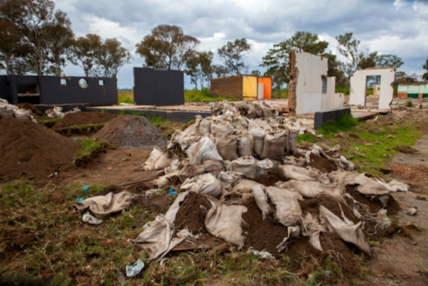 Bags of soil containing small amounts of gold sit slashed and abandoned after police forced illegal gold miners to destroy them. Behind the bags is what is left of the judo studio which operated in Durban Deep for over two decades. c. Julia Cumes