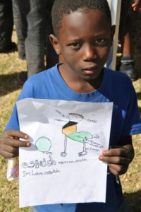 A child shows off his drawing of an animal.