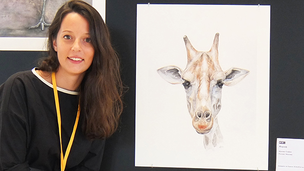 Shukhova stands beside one of her wildlife portraits. Photo courtesy of Sofiya S
