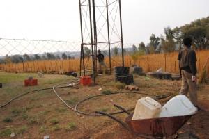 Der Brunnen auf dem Gelände des Ortsvorstehers, im Vordergrund der Junge, der Wasser kaufen will, im Hintergrund der Sohn des Vorstehers.