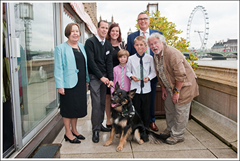 Geo the dog and family with Baroness Gale, IFAW UK Director Robbie Marsland and Bill Oddie.