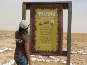 IFAW staffer reads a panel at the Amboseli Park Airstrip.