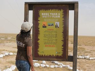 IFAW-Mitarbeiterin liest eine Infotafel bei der Flugzeuglandebahn im Amboseli-Nationalpark.
