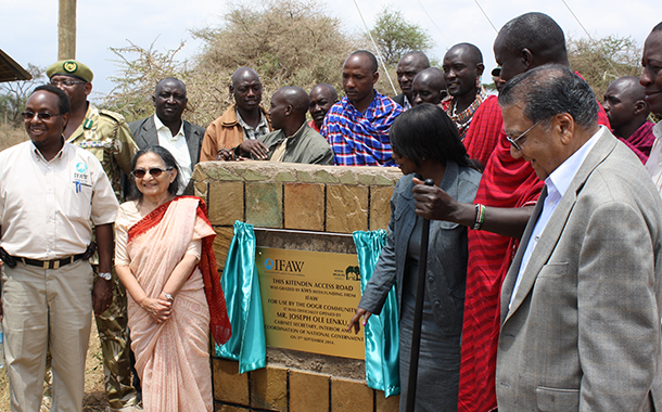 Invited guests and community members stand at the plaque of the Kitenden Access road. The road was graded with support from IFAW and Kenya Wildlife Service.