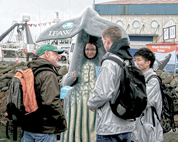 'Meet Us Don't Eat Us' volunteers ask tourists to sign a postcard that pledges not to eat whale meat and makes it clear that they are against whaling.