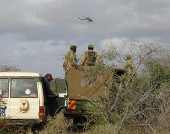 The ground team patiently waits for the radio calls from the helicopter on the position of the darted elephant.