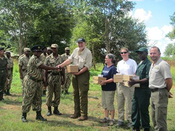 Ian Robinson, Dawn Smith and Katie Moore are presenting ZAWA Senior Warden Sulilo with new radios for use by the SAPU units.  Also in the picture are  r(right of Sulilo: SAPU senior commander Charles Mbao, Dane, Katie, SAPU Senior Support Manager Mr. Mulimo, and Sport Beattie (GRI, far right) and members of the SAPU unit.