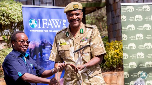 De auteur overhandigt één van de satellietzenders aan KWS-directeur Kitili Mbathi.