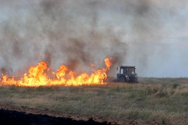 A tractor of one of the farmers from the Limansky District is fighting a wall of fire.