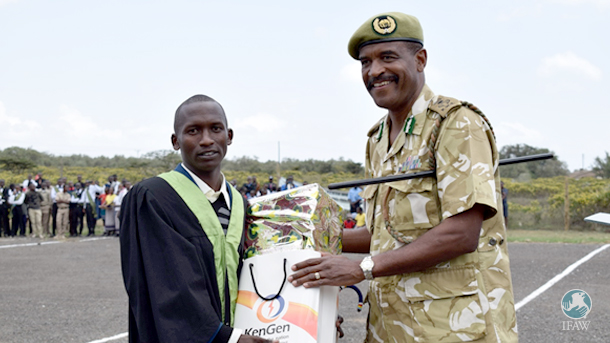 Samson Leposo receives a gift from KWS Director General Kitili Mbathi, the chief guest at the graduation at Kenya Wildlife Services Training Institute (KWSTI).
