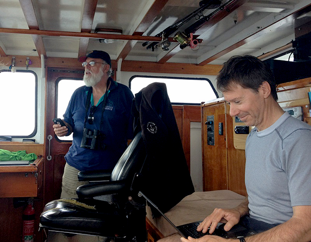 Dr Alastair Birtles, the Minke Whale Project's lead researcher scans for whales while Dr Russ Andrews, expert in whale tagging, tracks them on his laptop. Photo: © M. Collis
