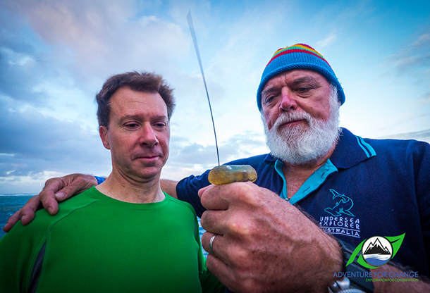 Dr Russ Andrews, expert in whale tagging, with Dr Alastair Birtles, the Minke Whale Project's lead researcher, holding the small tag that gets attached to the whales. Photo: © Adventure for Change