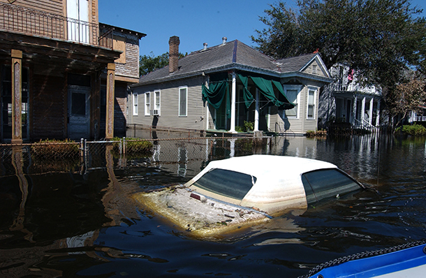 Flooded vehicles litter the streets of New Orleans neighborhoods.