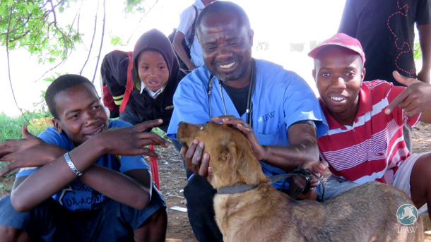 Dr Eric Mimbi, a CLAW vet, with one of the clinic patients and members of the township community the mobile clinic serves.