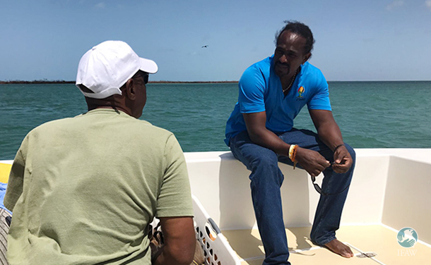 Alexander Desuza, a Barbuda Environment officer, speaks with another member of the Ministry of the Environment prior to arrival on Barbuda for a day of wildlife assessment.