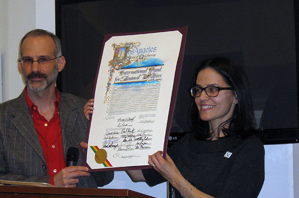 A National Museum of Animals and Society board member and the author hold the resolution from Mayor Garcetti and the entire L.A. City Council.