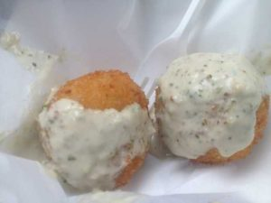 """""""First Love,"""" rice balls made with cilantro lime rice and a piece of carne asada inside. The rice balls are topped with an avocado sauce. (DFW Food Truck Foodie)"""