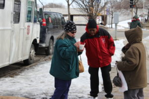 The Salvation Army's Director of Homeless Services, Christine Henry, helps steady a woman who had just got a free cup of hot soup from the charity organization's mobile outreach team.
