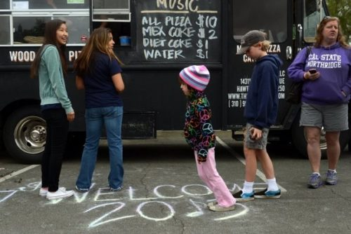 PHOTO BY KAREN QUINCY LOBERG, VENTURA COUNTY STAR // BUY THIS PHOTO Kate Johnson, 7, of Moorpark, plays a hybrid version of hopscotch/don't step on the lines while she waits for her food from The Urban Oven food truck Sunday at Conejo Creek Park in Thousand Oaks. Food trucks were the main draw to the Westlake High School music department's fundraising event, which also included live entertainment, a water balloon toss and a raffle.