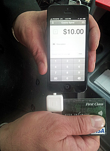 Cosmo Spina runs a credit card through a Square reader attached to his iPhone. (Courtesy Cosmo Spina)
