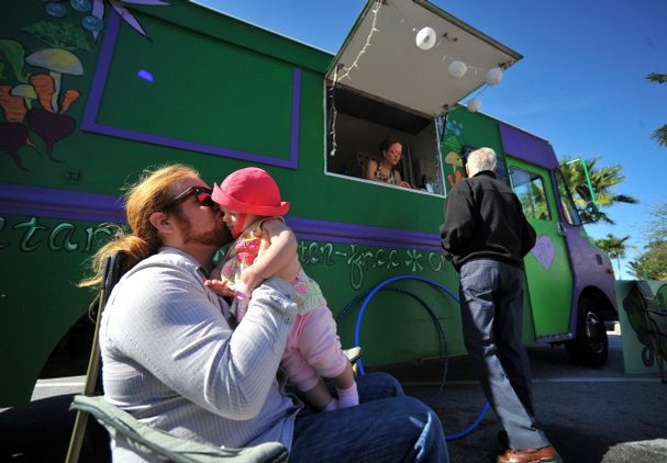 PHOTO BY ERIC HASERT, TREASURE COAST NEWSPAPERS  Elliott Ehrlich of Oregon holds his daughter, Maya Pearl, while waiting for their lunch order at the Veggie Love Truck.