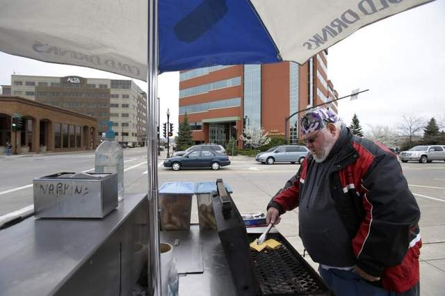 Richard Linskens, owner of Smoken Pig Express, cooks a double cheeseburger for a customer during lunchtime Friday in downtown Neenah. Linskens says a new $250 fee may prompt him to take his business to Menasha. / Dan Powers/Post-Crescent Media