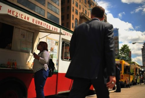 Tasha Hubbard, left, waits for her order from a food truck parked at Farragut… (Matt McClain/The Washington…)