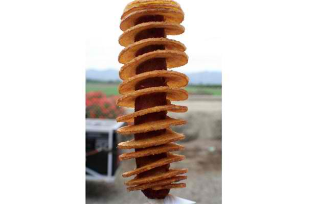 Chip dog: Not your typical meat and potatoes. Take your hotdog on a stick and then surround it by spiral cut chips. Photograph by: Courtesy, Calgary Stampede