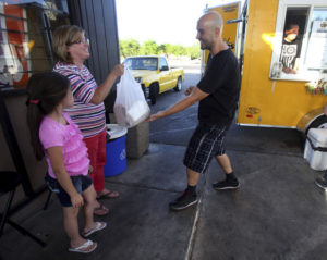 Mike Christy / Arizona Daily Sta Jeremy Geyer brings a Serial Grillers order to Cindy Zufelt and her daughter Celeste, 8. A mister system underneath a canopy keeps things cool.