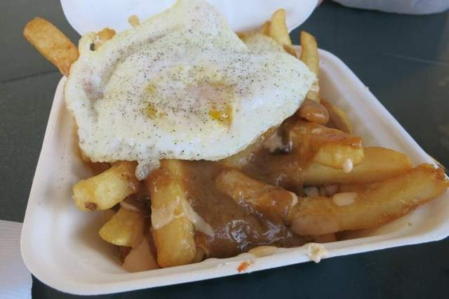 A fried egg tops an order of sizzling hot poutine for breakfast — or any time — at the Mac Shack food truck in Eastern Market. It is one of six trucks that will be at the market Tuesday, July 30, from 9 a.m. to 3 p.m. / Sylvia Rector/Detroit Free Press