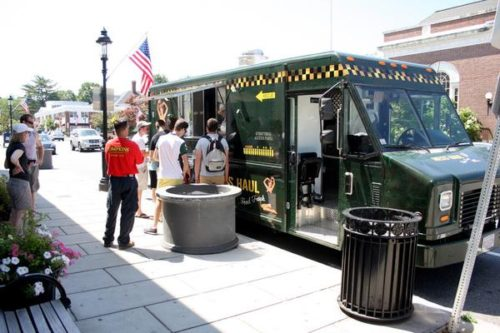 Customers line up at Mess Haul in downtown Andover. The mobile eatery recently picked up a parking ticket for exceeding parking limits. Some in town are suggesting a need to create designated areas for the growing number of food trucks in Andover. DUSTIN LUCA/Staff Photo