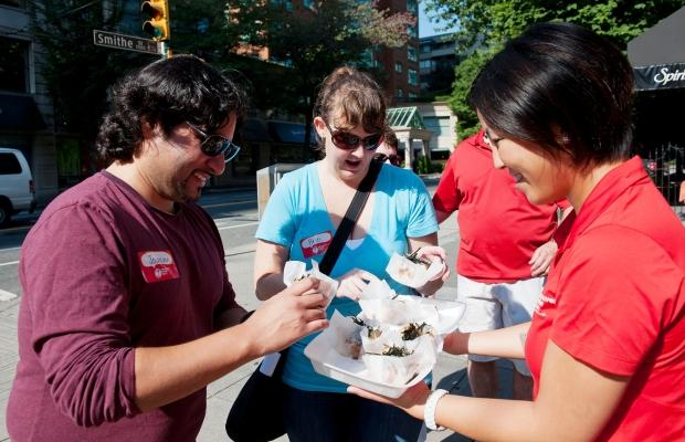 Joaquin Reyes and Brie Horigan sample a Japadog with tour guide Michelle Ng while at the first stop on the World's Best Food Truck Tour on the corner of Smithe and Burrard. Photograph by: RICHARD LAM, PNG