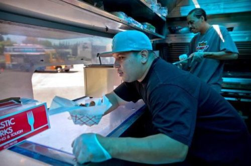 A.J. Navarro, left, serves food with Craig Williams, right, inside his mobile food truck, Gameday Grill, on Tuesday.