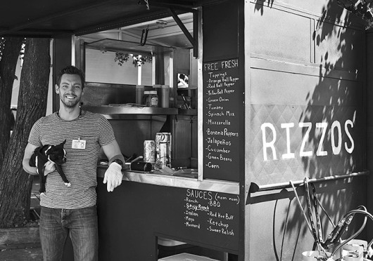 Ray Kinne, a 5th-year in photography, poses with his Boston Terrier, Rizzo, in front of his food cart, Rizzo's Eats, which is usually located at 14th Avenue and High Street. Credit: Courtesy of Ken Snow
