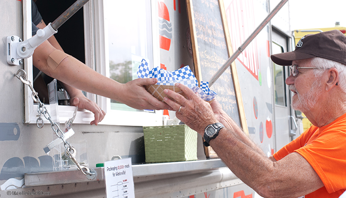 by Stephanie Parker / Otterbein360 A customer at the Challah Food Truck is handed his purchase.