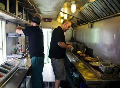 Jake Baniky, left, and John D'Elia work inside their Urban Bamboo food truck in Anchorage, Alaska. (AP File Photo/Marc Lester)