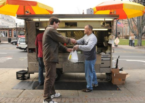 James McGinniss pays Elsayad Abdelgalio a co-owner of The New York Halal Food cart last fall. Abdelgalio's cart is one of three such operations that have been stationed in downtown Amherst. Northampton City Council has signaled they'd like to reconsider the city's ban on food trucks.