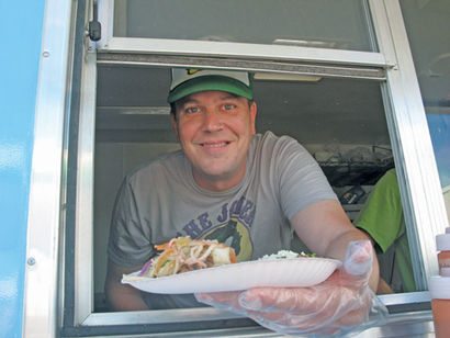 Dia de los Tacos food truck owner Mike Walker hands tacos out the window of his mobile restaurant. Walker's business was one of eight food trucks in the state to receive grant funding from the Michigan Economic Development Corp. as part of its Mobile Cuisine Start up Program. (Journal photos by Jackie Stark)