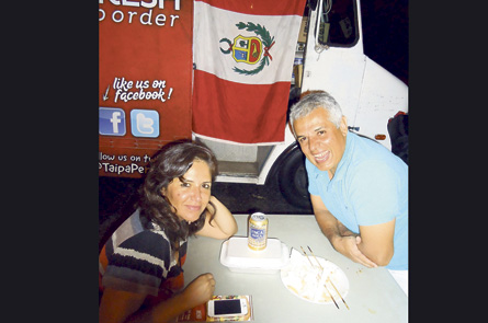 Happy customers of Taipa Peruvian Fast Food Truck, Nelly and Enrique Doria, follow their Peruvian flag (in background) and Peruvian food anywhere they can.