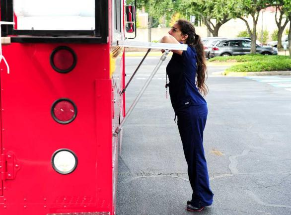 EMILY ROSE BENNETT/STAFF Graduate student Remi Elkattah, 25, orders at Laziza Mediterranean Grill food truck outside the student center at Georgia Regents University's Health Science campus as it undergoes installation of new dining options.